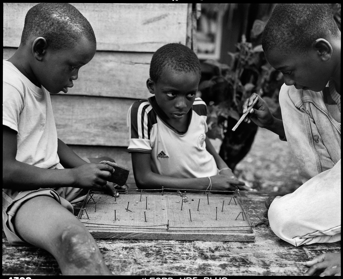 Photograph of Children in Puente Nayero playing an improvised game of table football