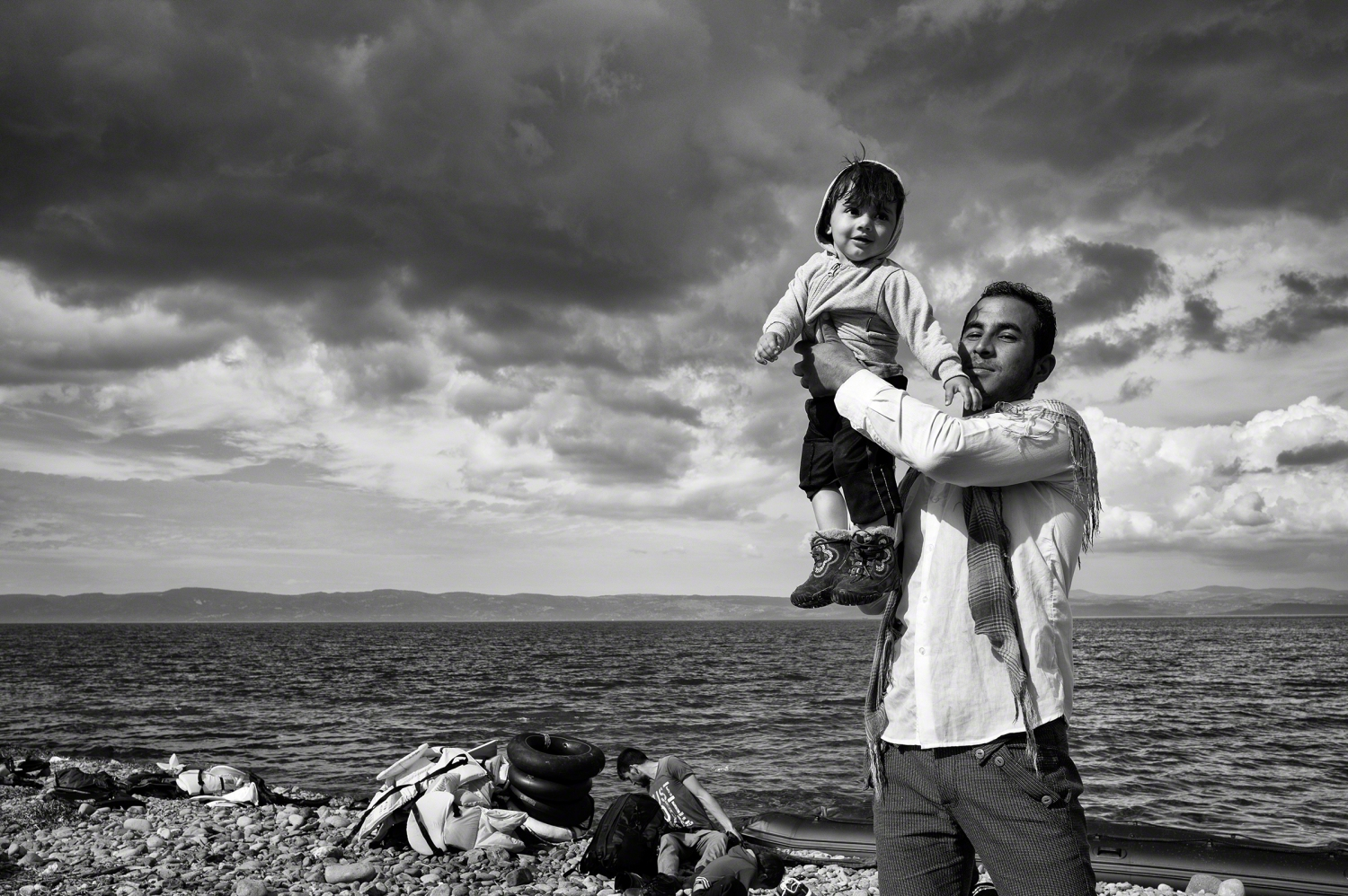 A black and white photograph of a father raising his young child to celebrate his family's safe passage to Lesbos after crossing over the Aegean Sea from Turkey