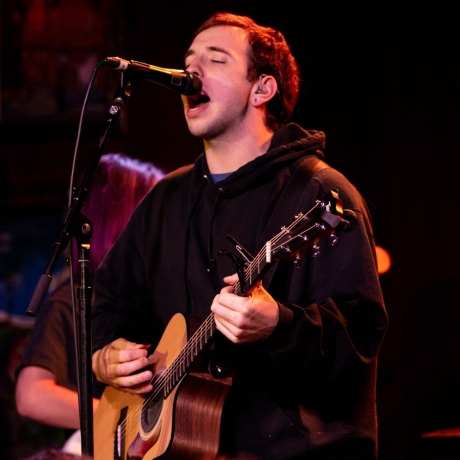 A picture of singer and songwriter Mat Kerekes holding a guitar on stage