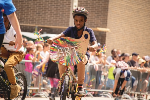 a young african american child on a colorfully decorated bicycle