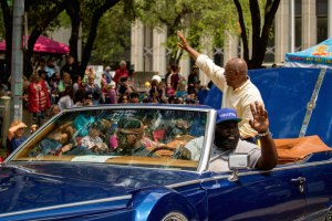 a picture of Mayor Sylvester Turner in the back seat of a brightly painted classic convertible