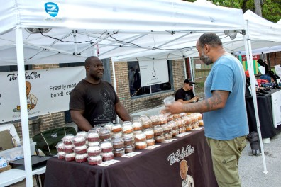 A picture of a customer customer standing at a vendor's table with many miniature bundt cakes