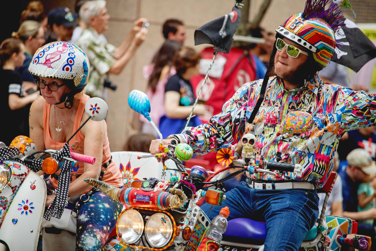 a picture of a couple riding scooters wearing eccentric costuming