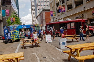 A picture of two food trucks and picnic tables on a downtown city street